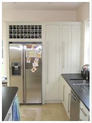 Housing for side by side fridge freezer with integral wine rack, appliance cupboard with bifold door shown closed. Detail from bespoke kitchen designed by Cameron Pyke of Celtica Kitchens, Celtica Heritage