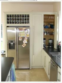 Housing for American fridge freezer with integral wine rack, tea and coffee cupboard with bifold door shown open. Detail from bespoke kitchen, designer  Cameron Pyke, Celtica Heritage